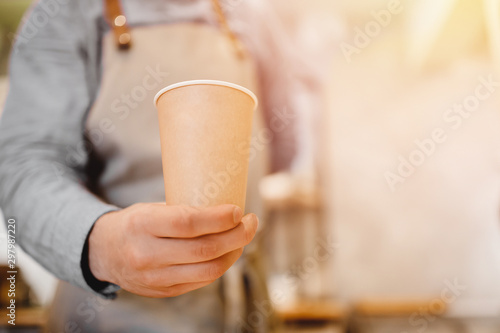 Papiers peints Cafe Blurred background barista holds cardboard glass of coffee, glare of light, copy space