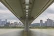 River water and urban architectural landscape at the bottom of single-column concrete bridge