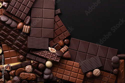 obraz lub plakat dark chocolate background, sweet bar and candy with empty space for text