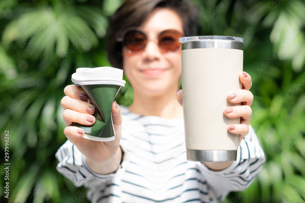 Fototapeta A stylish beautiful woman holding takeaway coffee cup in both hands, one is a single use paper cup with plastic lid the other one is a reusable stainless tumbler. No straw and Zero waste concept.