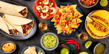 A Panorama Of Mexican Food, Many Dishes Of The Cuisine Of Mexico, Flatlay, Shot From The Top On A Black Background. Nachos, Tequila, Guacamole Etc