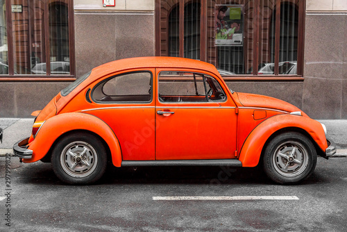 Fototapeta BUDAPEST, SEPTEMBER 17: Orange retro car Volkswagen Beetle parked on the old street on September 17, 2016 in Budapest, Hungary