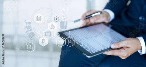 Cuadros en Lienzo Health care insurance concept, Businessman completing a medical claim form with insurance icon health care on tablet digital
