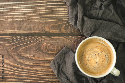 Canvas Prints Cafe Close-up of Cappuccino or latte coffee with milk foam in white ceramic cup coffee and napkin on natural wood texture background. top view with copy space.