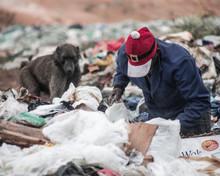 A Man Rummages Through Trash A...