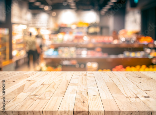Fotomural Wood texture table top (counter bar) with blur grocery,market store background