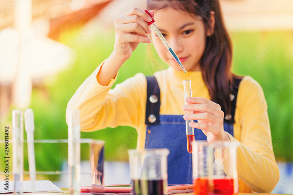 Fototapety, obrazy: Asian teenage girl in elementary science class doing chemical experiment test try to drop color water to test tubes. Education concept. Selected focus