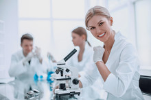 Successful Female Scientist Sitting In Front Of A Microscope