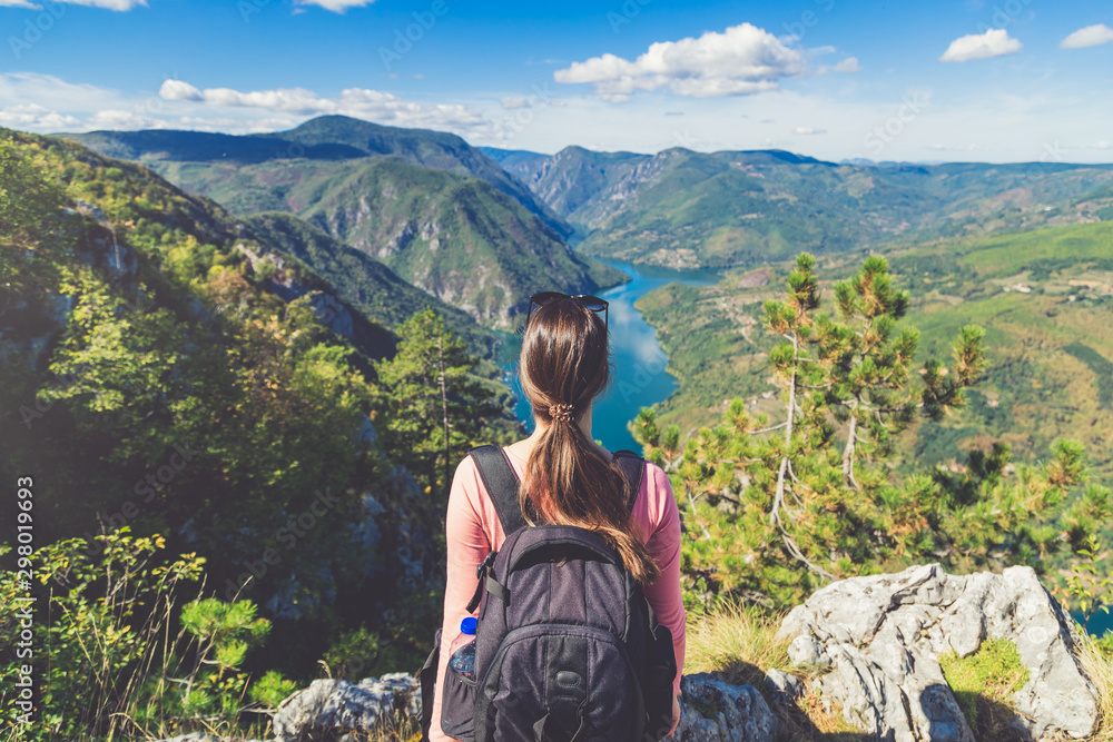 Fototapety, obrazy: Young female backpacker sitting on rock at mountain top and enjoying the nature view of beautiful valley lake or river with hills.