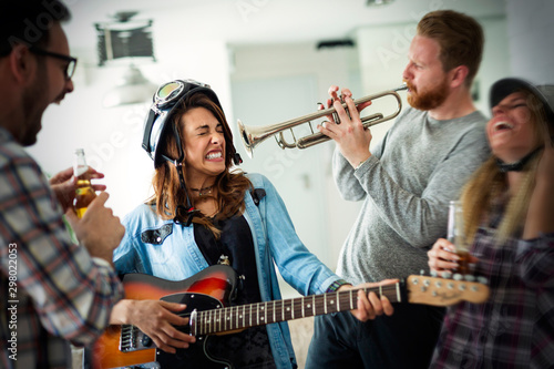 Group of friends at home enjoying singing and playing guitar Poster Mural XXL