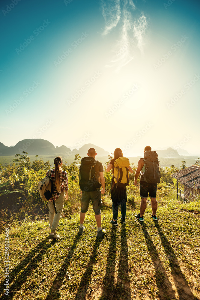 Fototapety, obrazy: Four hikers and travellers at sunrise sea viewpoint
