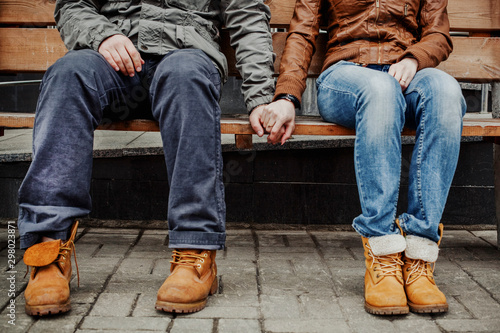 Fotografía  Loving hipster couple in jeans and rough boots sitting on a bench and holding ha