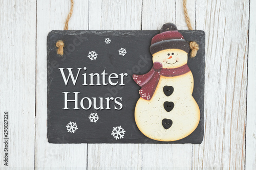 Obraz na plátne  Winter Hours hanging chalkboard sign with a snowman