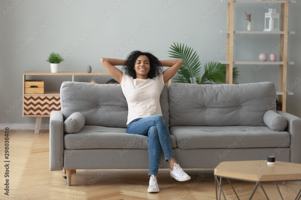 Fototapeta Happy black girl relaxing on cozy sofa at home