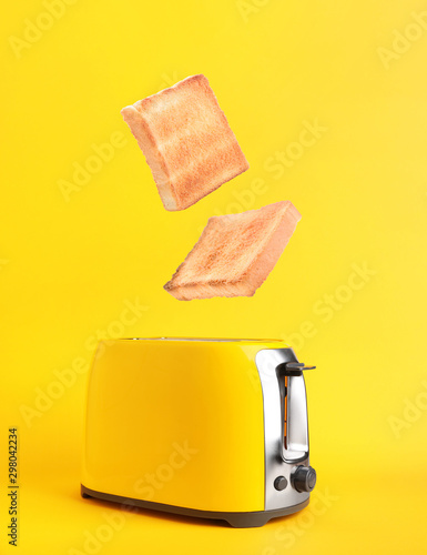 Toaster with bread slices on color background Canvas Print