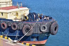 Tug Ship Bow With Large Rubber Wheels. Big Tires Of The Deck Of A Tug Boat. Tire Safety Bumper On The Bow Of The Tugboat. Tugboat Details