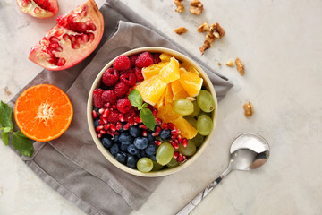 Bowl with tasty fruit salad on light background