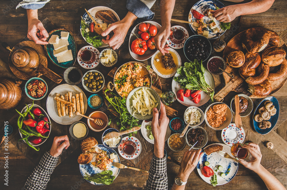 Fototapety, obrazy: Turkish breakfast table. Flat-lay of peoples hands taking pastries, vegetables, greens, olives, cheeses, fried eggs, jams, honey, tea in copper pot and tulip glasses, top view. Middle Eastern meal