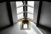 Interior, Roof Space View Of An Historic Building Showing The Large Skylight Windows. A Medieval Arch Window Is Also Seen, Contrasting Shadows Are Also Seen