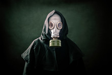 Man In A Gas Mask And Hooded Cloak. Environment Pollution.