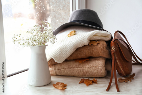 Stack of warm clothes with flowers on window sill