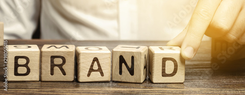Fotografering Businessman puts wooden blocks with the word Brand