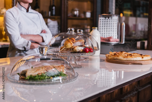 Valokuvatapetti Unrecognizable Female Chef standing over Buffet Table with food