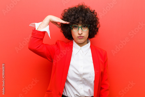 young pretty afro woman greeting the camera with a military salute in an act ...