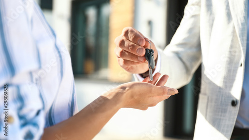 Photo Stands Amsterdam Real estate agent giving house keys to young woman outdoors, closeup