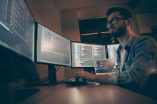 Profile Side View Of Nice Attractive Serious Skilled Qualified Smart Clever Bearded Brunet Guy Nerd Building Fixing Extracting File Editing Framework Web Design In Dark Beige Room Workplace Station