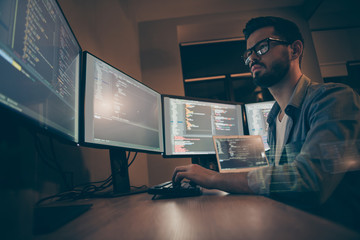 Obraz na płótnie Canvas Profile side view of nice attractive serious skilled qualified smart clever bearded brunet guy nerd building fixing extracting file editing framework web design in dark beige room workplace station