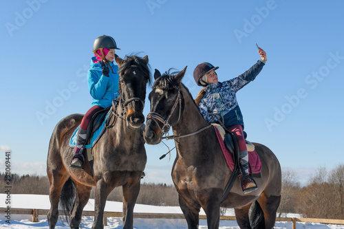 Photo Two caucasian female teenager, 13 years old, are astride their horses and taking a selfie with one smartphone on the training arena in winter