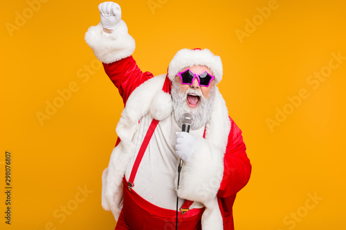 Grey haired stylish christmas grandfather in red hat cap celebrate x-mas party hold microphone sing noel carols feel funky with big belly wear suspenders isolated over yellow color background