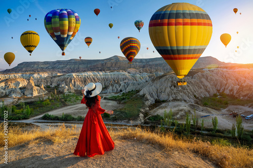 Beautiful girl standing and looking to hot air balloons in Cappadocia, Turkey Wallpaper Mural