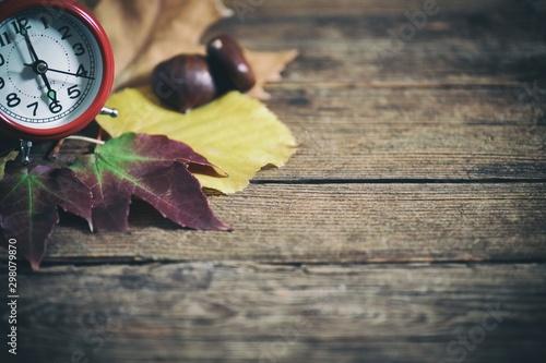 Composizione di foglie autunnali e orologio sveglia su un tavolo in legno Fototapeta