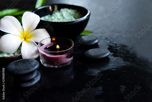 Fototapeta Thai Spa. Top view of white Plumeria flower setting for massage treatment and relax on concrete blackboard with copy space. Green leaf with black stones pile for spa therapy. Healthy Concept.
