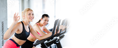 Fotomural Women wearing sportswear doing workout activity, spinning an electric bicycle in the gym For good health Have a beautiful shape And allowing the muscles to relax