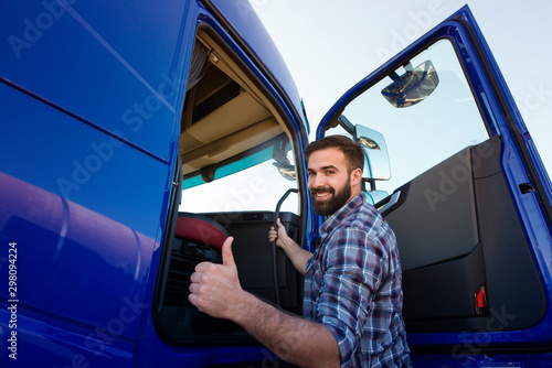 Obraz Professional truck driver entering his truck long vehicle and holding thumbs up. Loving his job. Transportation services. - fototapety do salonu