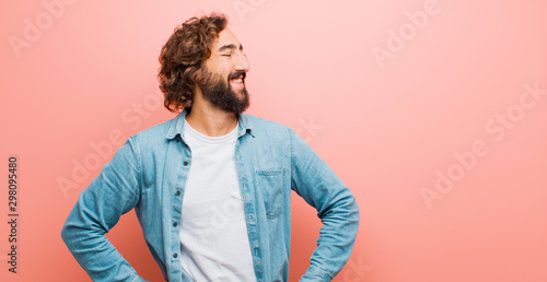 Pinturas sobre lienzo  young bearded crazy man looking happy, cheerful and confident, smiling proudly a