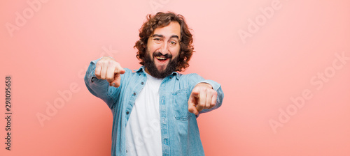 Fototapeta young bearded crazy man feeling happy and confident, pointing to camera with both hands and laughing, choosing you against flat color wall obraz