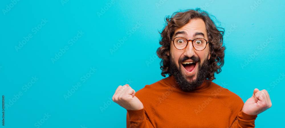 Fototapeta young bearded crazy man feeling shocked, excited and happy, laughing and celebrating success, saying wow! against flat color wall