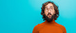 Leinwanddruck Bild - young bearded crazy man with a worried, confused, clueless expression, looking up to copy space, doubting against flat color wall