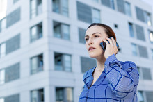 Beautiful Businesswoman In Blue Checkered Shirt Frowning And Looking Away While Standing On Blurred Background Of Modern Building On City Street