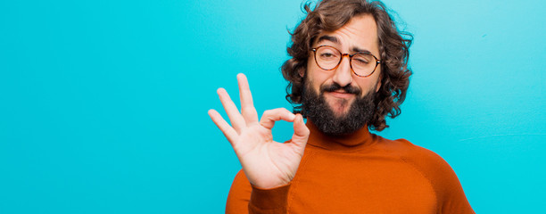 young bearded crazy man feeling happy, relaxed and satisfied, showing approval with okay gesture, smiling against flat color wall