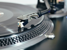 Closeup Of Top Of Old Black Turntable With Tonearm Maintaining Position Of Cartridge Tracing Groove And Playing LP Record