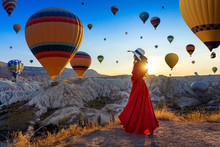 Beautiful Girl Standing And Looking To Hot Air Balloons In Cappadocia, Turkey.
