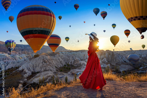 Photo  Beautiful girl standing and looking to hot air balloons in Cappadocia, Turkey