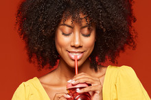 Close-up View Of Dreamy Young African American Lady With Curly Hair Holding Red Jar With Straw And Enjoying Beverage On Red Background