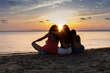 Back View Of Bronzed Female Friends Hugging And Relaxing On Beach At Sunset In Summer In Back Lit