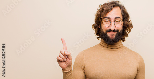 Fototapeta young bearded crazy man smiling cheerfully and happily, pointing upwards with one hand to copy space against flat color wall obraz